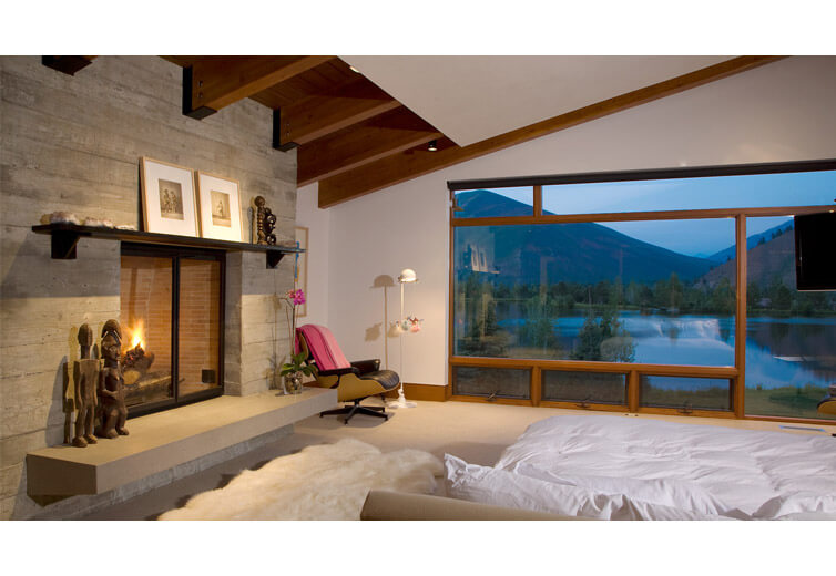 Interior shot of the master bedroom at twilight with views onto the pond and mountains beyond.  Interior design in a contemporary style with mountain influences.  Exposed timber beams and concrete.