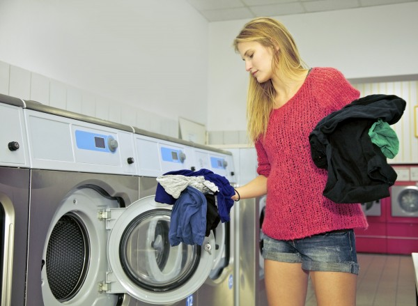 Young woman loading a washing machine inside a laundromat shop.