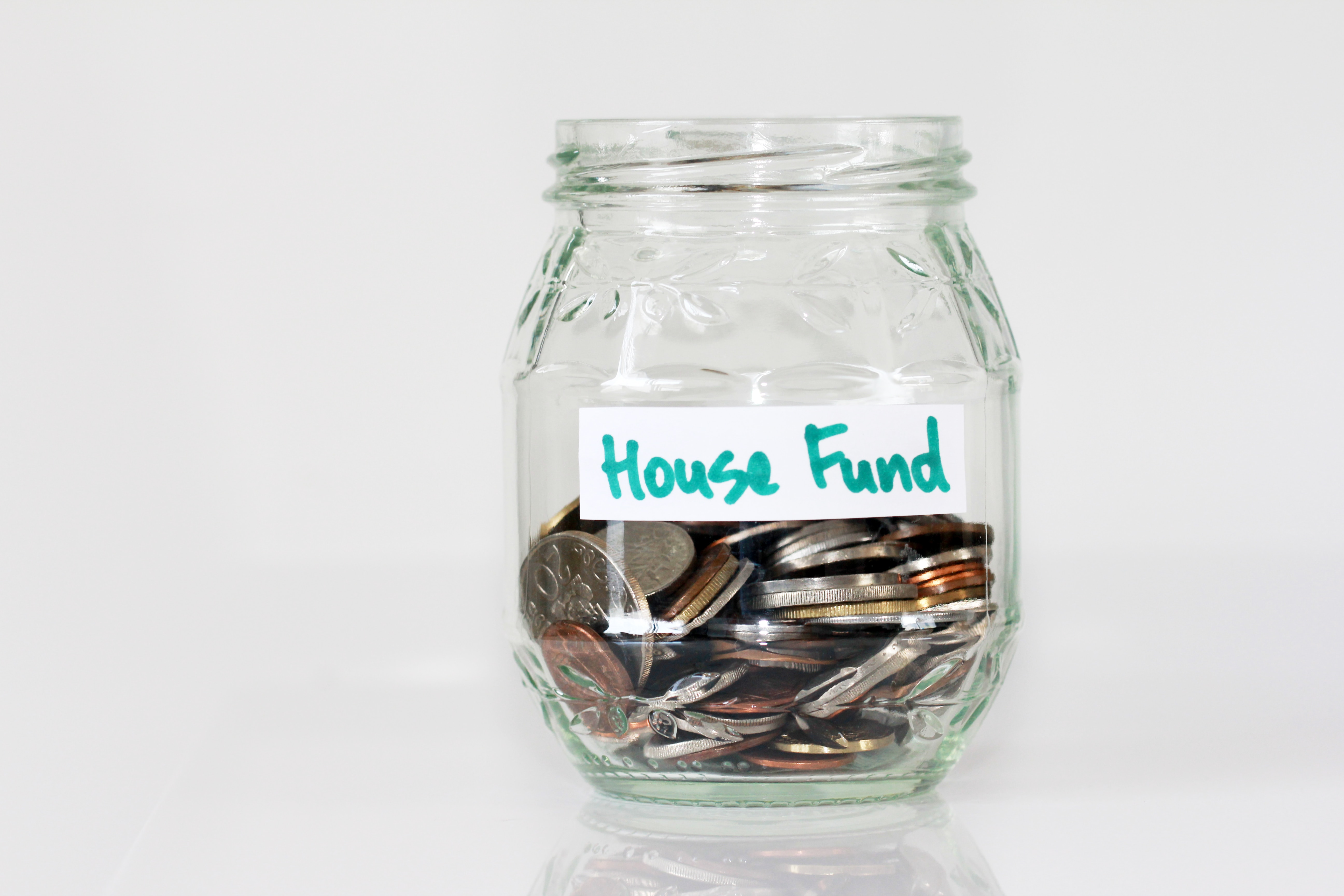 coins in clear glass jar with house fund sign